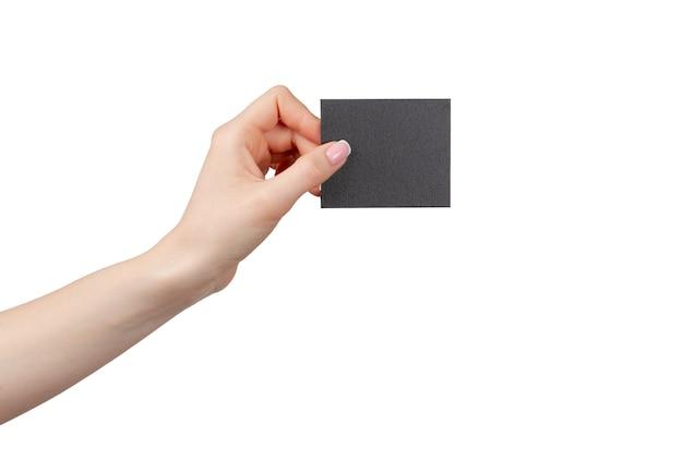 Mano femminile che tiene businesscard nero isolato su sfondo bianco, copia dello spazio
