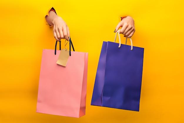 Mano femminile che tiene le borse della spesa luminose su giallo attraverso una carta strappata