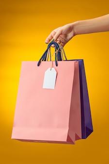 Mano femminile che tiene le borse della spesa luminose su giallo