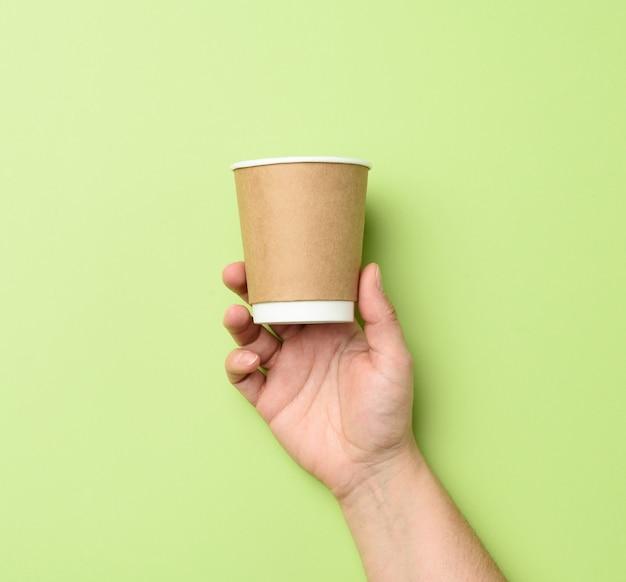 Mano femminile che tiene tazza usa e getta di carta marrone su verde