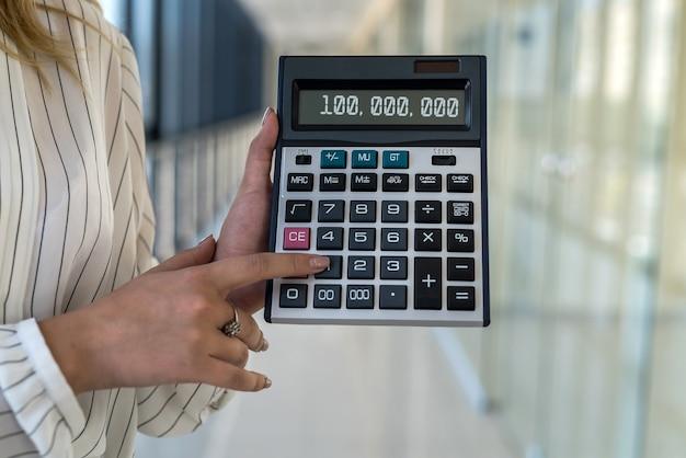 Calcolatrice femminile della tenuta della mano nel centro di affari moderno. concetto di finanza