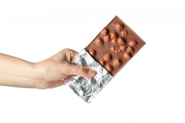 Barra di cioccolato femminile della tenuta della mano, isolata su bianco