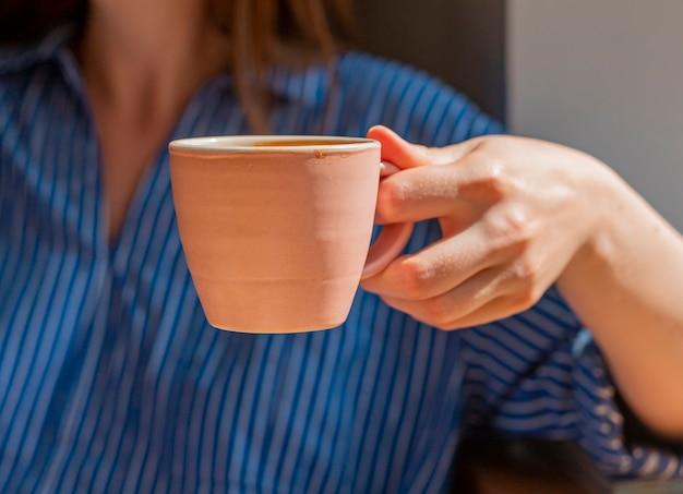 Primo piano femminile della tazza di caffè della tenuta della mano