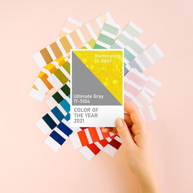 Mano femminile che tiene i colori dell'anno 2021 - ultimate grey e illuminante con campioni di colore alla moda. tavolozza di tendenza dei colori.