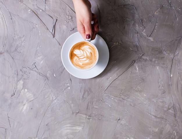 Mano femminile che tiene una tazza di cappuccino con crema di figura. vista dall'alto con copia spazio