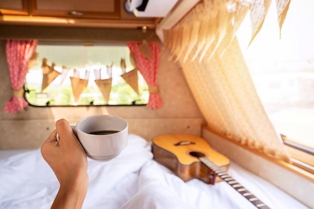 Mano femminile che tiene una tazza di caffè all'interno del camper con una chitarra sul letto e una bella luce solare