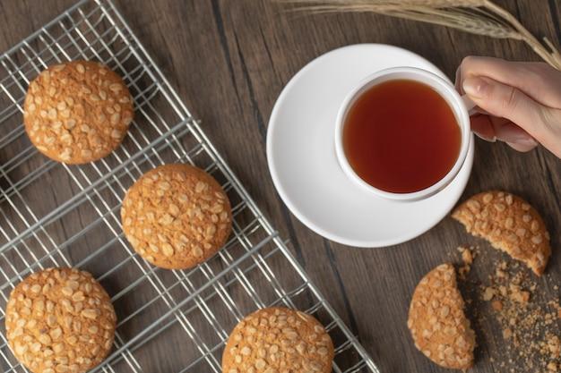 Mano femminile che tiene tazza di tè caldo sulla tavola di legno