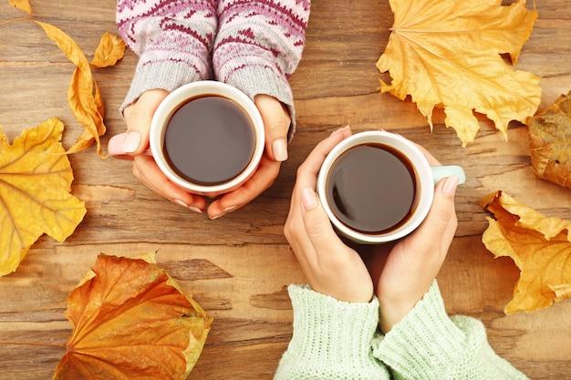 Mano femminile che tiene le tazze di caffè con le foglie di autunno sul fondo di legno rustico della tavola