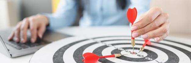 Mano femminile che tiene il dardo nel centro del dardo al tavolo di lavoro impostazione degli obiettivi nel concetto di business