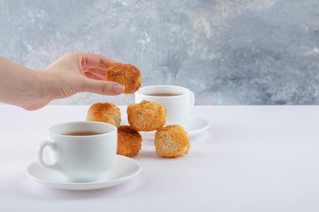 Mano femminile che tiene biscotto croccante fatto in casa delizioso vicino a tazze bianche di tè caldo.