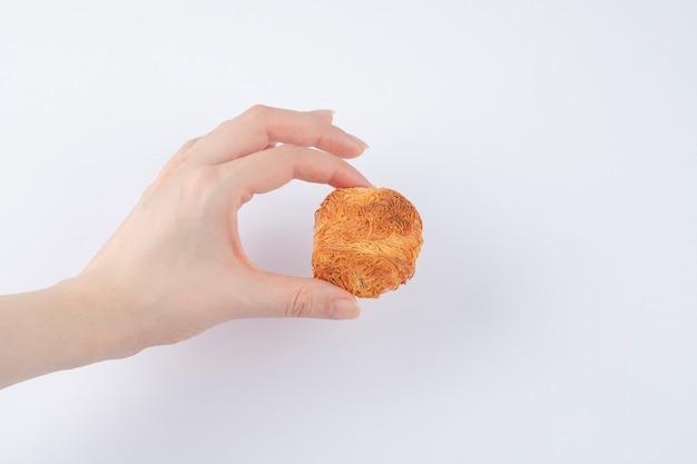 Mano femminile che tiene biscotto croccante fatto in casa delizioso su un tavolo bianco.