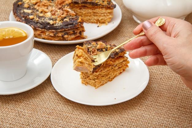Mano femminile che tiene una forchetta e va ad assaggiare la torta al cioccolato fatta in casa sdraiata su un piattino bianco con un sacco sullo sfondo.