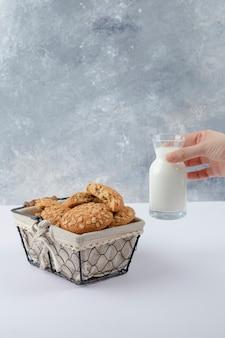 Mano femminile che tiene una brocca di vetro di latte vicino ai biscotti di farina d'avena con i semi.