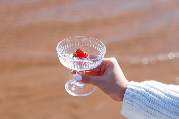 Mano femminile che tiene bicchiere d'acqua con fragola sul mare sullo sfondo della sabbia sand