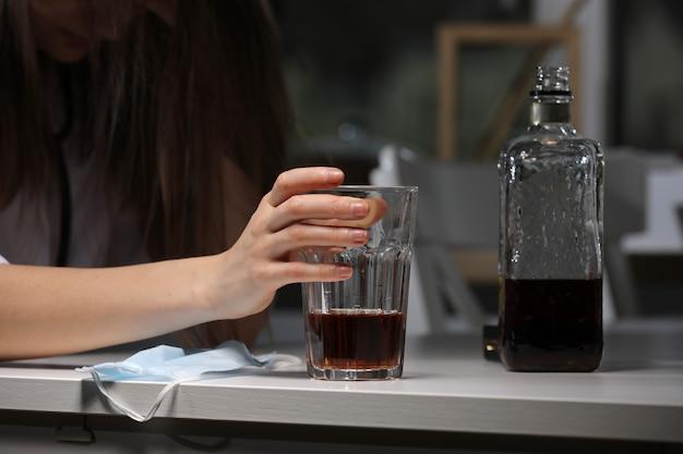 Mano femminile che tiene vetro con bevanda alcolica. maschera per il viso.