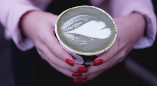 Mano femminile che tiene il latte caldo di matcha del tè verde in tazza di carta. unghie rosse