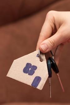 Chiave di casa femminile della tenuta della mano, agente immobiliare.