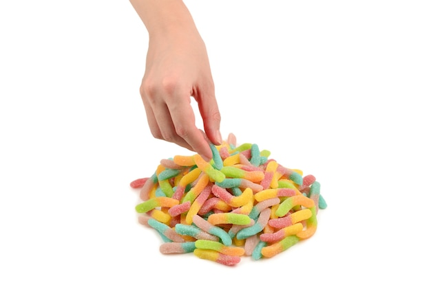 Mano femminile che tiene i dolci della gelatina isolati su fondo bianco