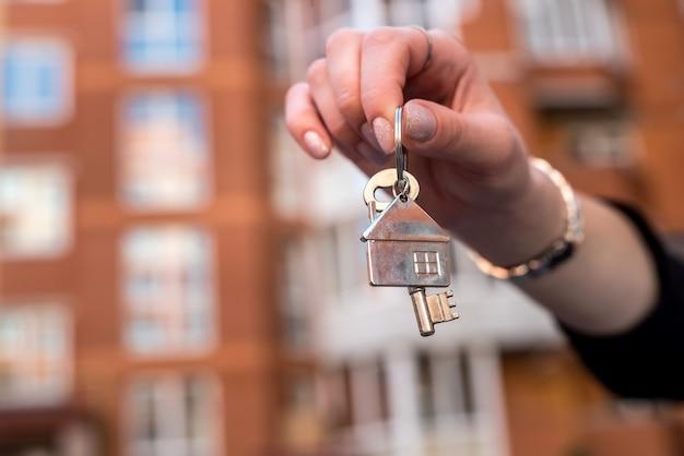 Mano femminile che tiene le chiavi davanti a una nuova casa.