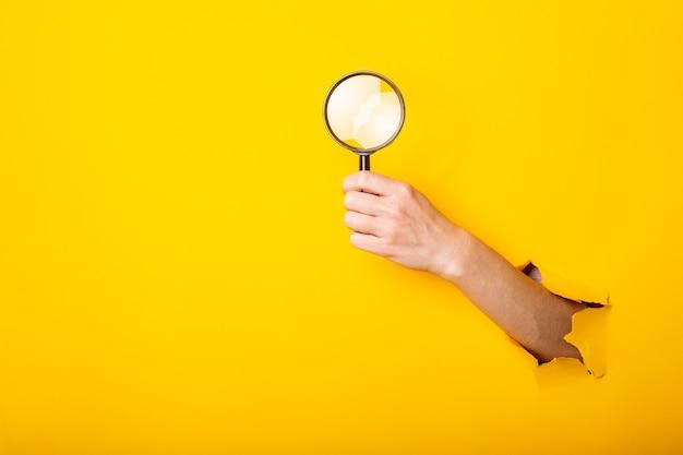 Mano femminile che tiene lente di ingrandimento lente di ingrandimento su sfondo giallo strappato.
