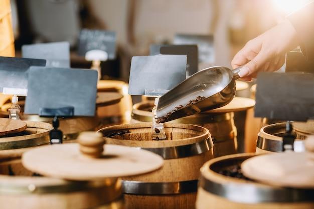 Una mano femminile che tiene una paletta di metallo piena di chicchi di caffè nella caffetteria