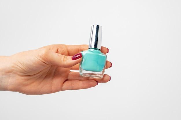 Mano femminile che tiene lo smalto per unghie contro uno sfondo bianco vicino