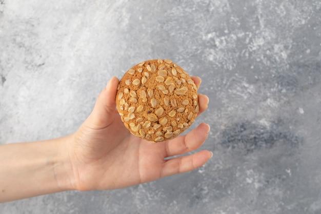 Mano femminile che tiene i biscotti di farina d'avena con i semi sulla superficie di marmo