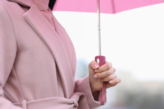 Mano femminile che tiene ombrello rosa in primo piano di pioggia. concetto di previsioni del tempo