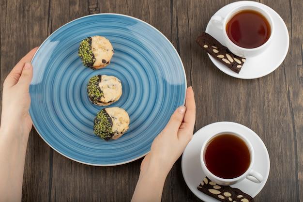 Mano femminile che tiene un piatto con biscotti e tazze di tè.