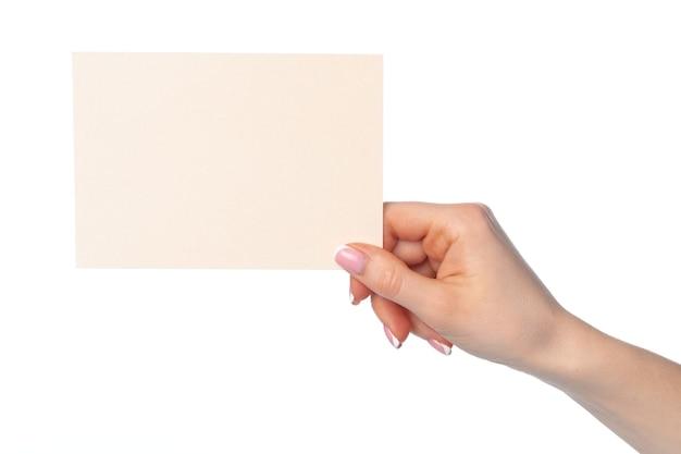 Mano femminile che tiene foglio di carta isolato su sfondo bianco