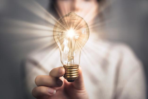 Mano femminile che tiene una lampadina splendente, grande idea, innovazione e ispirazione, design retrò moderno del fondo di concetto di affari