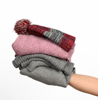 Mano femminile che tiene una pila di vestiti, aiuto e concetto di volontariato. ordinamento delle cose