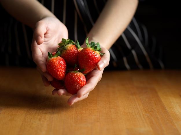 Mano femminile che tiene le fragole sul tavolo da cucina in legno
