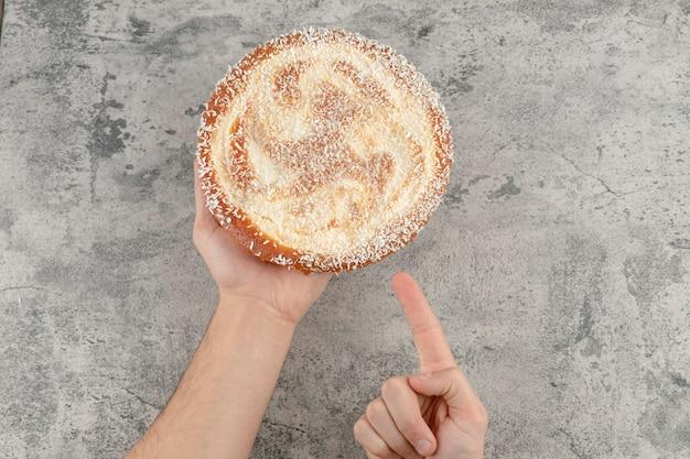 Mano femminile che tiene la torta di mele dolce sulla superficie di marmo.