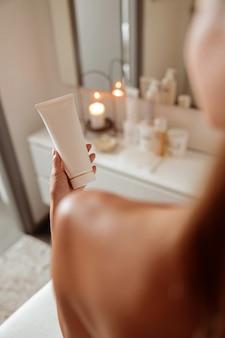Mano femminile che tiene il tubo di crema o lozione cosmetica