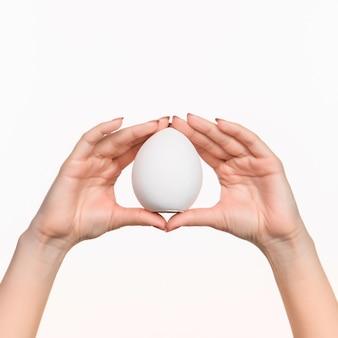 La mano femminile che tiene l'ovale di polistirolo bianco bianco sullo sfondo bianco con l'ombra giusta