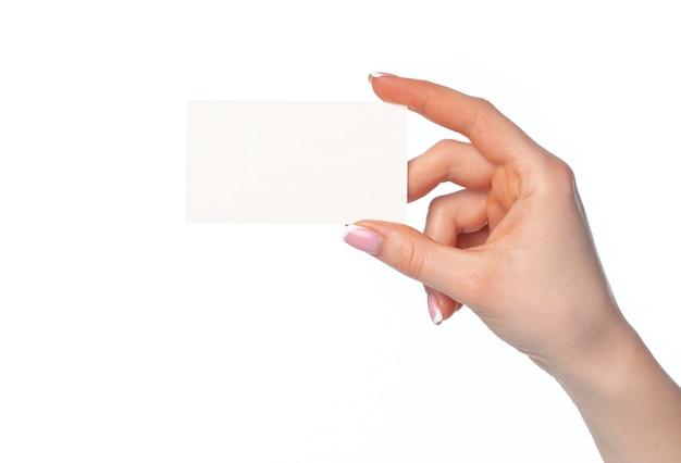 Mano femminile che tiene biglietto da visita bianco isolato su priorità bassa bianca