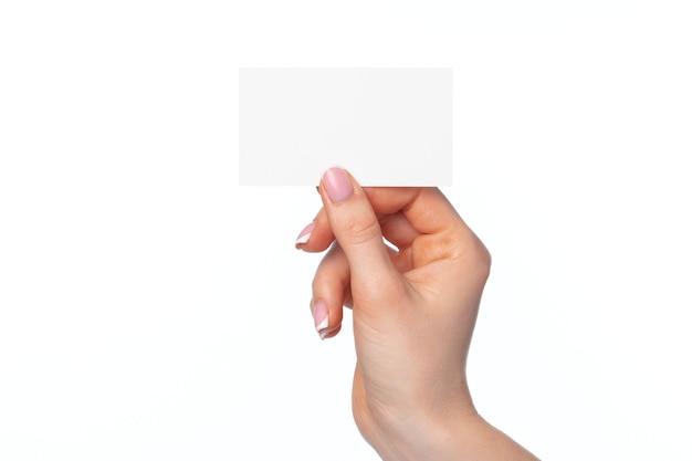 Mano femminile che tiene biglietto da visita bianco isolato su bianco