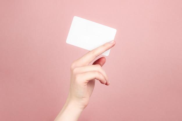 Mano femminile che tiene biglietto da visita bianco
