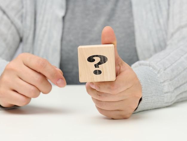 Mano femminile che tiene un cubo di legno con un punto interrogativo, concetto di risposte e domande, suspense e metodi di soluzione, primo piano