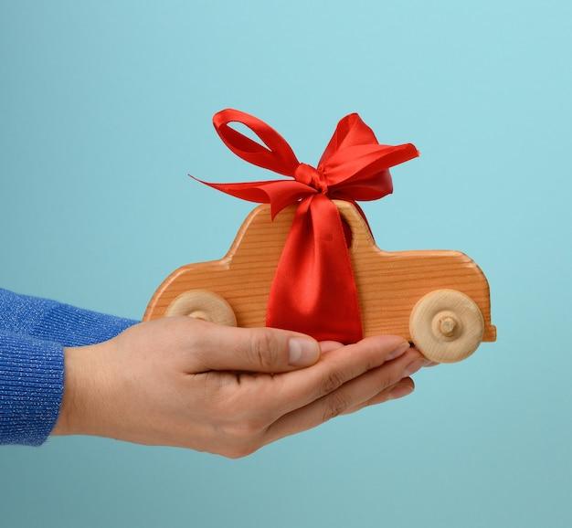 Mano femminile che tiene automobile del giocattolo di legno con il nastro rosso sulla superficie blu, concetto di assicurazione auto, prestito