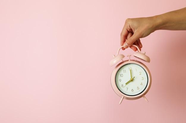La mano femminile tiene la sveglia sul rosa
