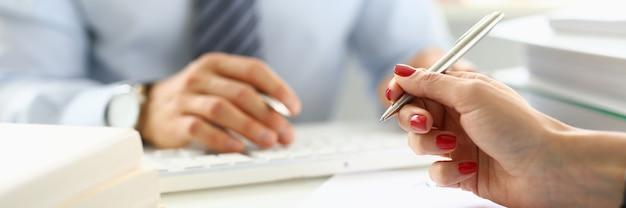 La mano femminile tiene la penna a sfera sopra il primo piano dei documenti davanti all'uomo in ufficio. conclusione concetto di riunione d'affari.