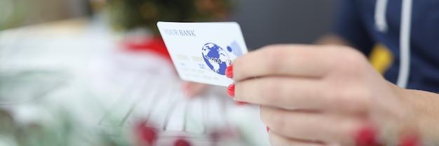 La mano femminile tiene la carta di plastica di credito della banca