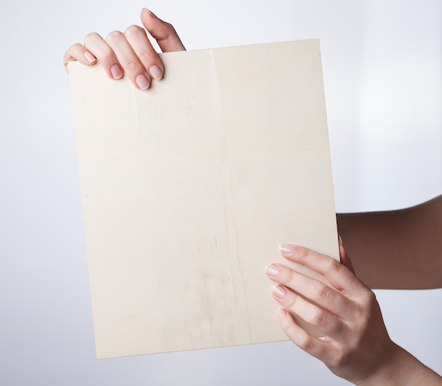 La mano femminile tiene il tabellone per le affissioni in bianco