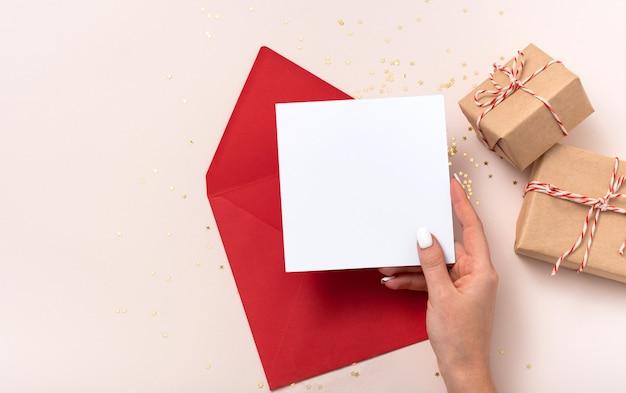 La mano femminile tiene il natale rosso della busta del modello di carta quadrata vuota