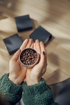 Mano femminile tiene una ciotola di caffè macinato e fagioli in confezione regalo sul tavolo, primi piani.