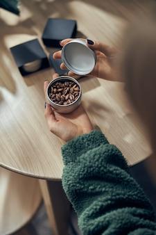 La mano femminile tiene la ciotola di caffè macinato e fagioli in confezione regalo sul tavolo.