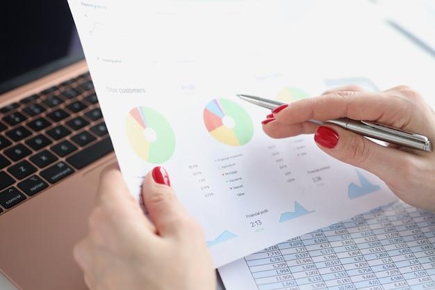 La mano femminile tiene grafici aziendali con indicatori commerciali e previsioni di penna sul posto di lavoro