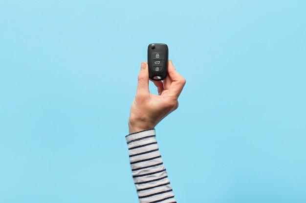 La mano femminile tiene le chiavi dell'automobile su un fondo blu. concept car, noleggio auto, regali, lezioni di guida, patente di guida.